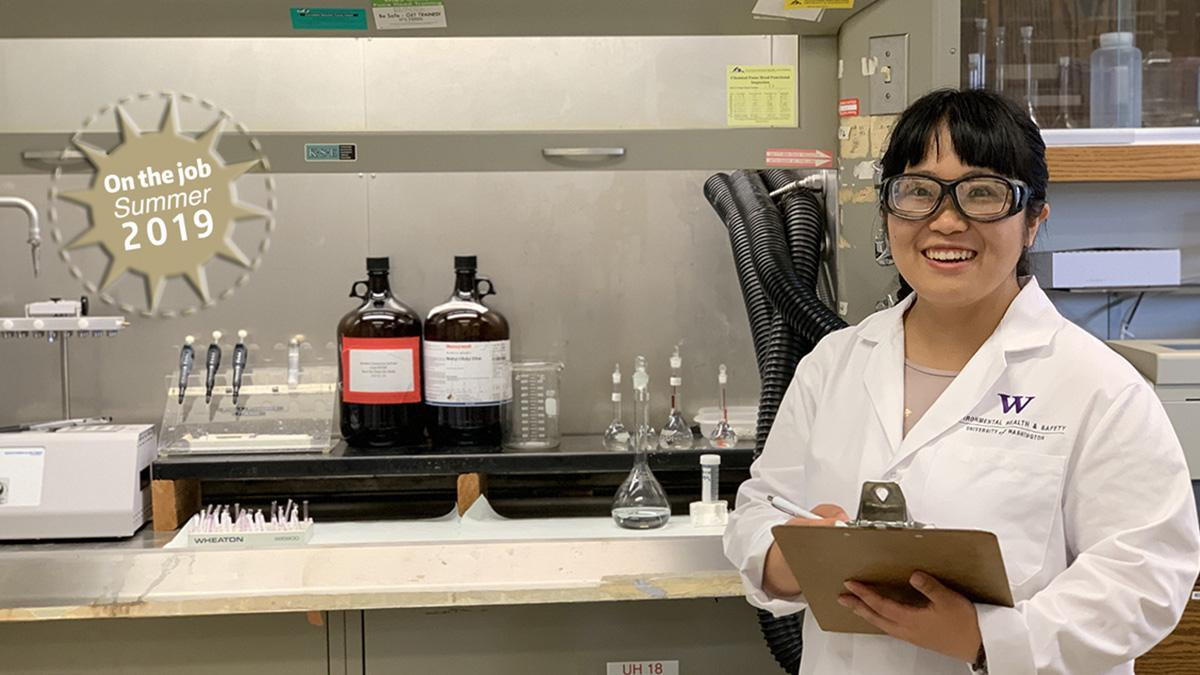 A young woman wearing a lab coat and safety goggles stands in a University of Washington laboratory.
