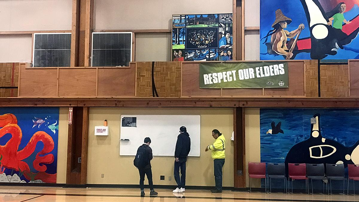 Three people stand in a gym near a whiteboard on a wall decorated with Native American art.