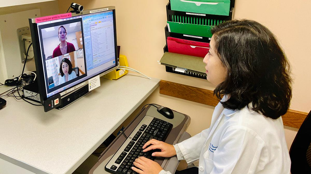 A doctor sits in front of a computer with a video image of herself and a patient.