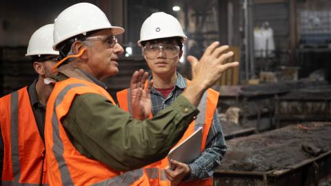 A man in a hardhat and orange vest speaks to student wearing the same safety gear in an industrial setting.