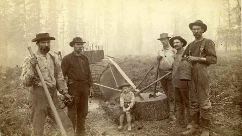 Black and white image of five loggers and a boy in Western Washington, W. T. The men are standing with axes in hand appearing to have just cut down a tree. The boy sits on the stump.