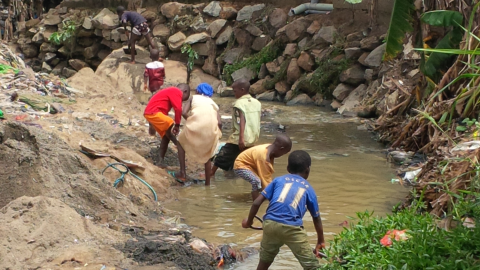 Children in Nigeria playing in water in a drainage area contaminated by wastewater.