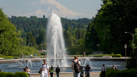 A group of students walk and bike around a fountain with a view of a snow-covered mountain in the distance.