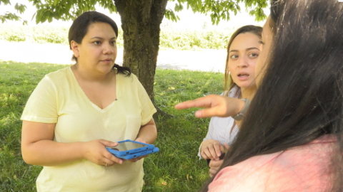 Three women stand outside talking, one holding a computer tablet.