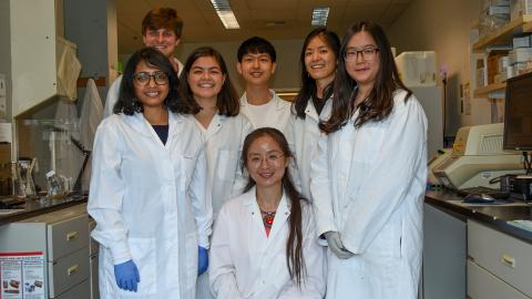 A team in labcoats poses in their lab.