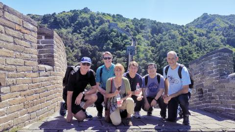Six people smiling and kneeling on a brick walkway that is part of the Great Wall of China.