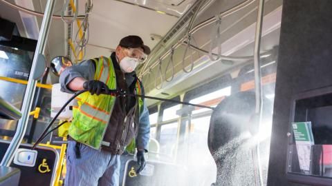 A man in a face mask and protective gear uses a spray wand to spray disinfectant inside a bus.