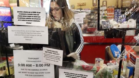A grocery store clerk stands behind a clear plastic shield filled with signs about COVID-19 while scanning groceries..