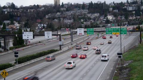 Cars drive along highway I-5 in Seattle with the houses and buildings of Beacon Hill in the background.