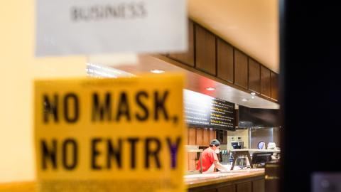 "A sign on a door reads ""No Mask No Entry"" as a worker in a face mask cleans a counter in the background."