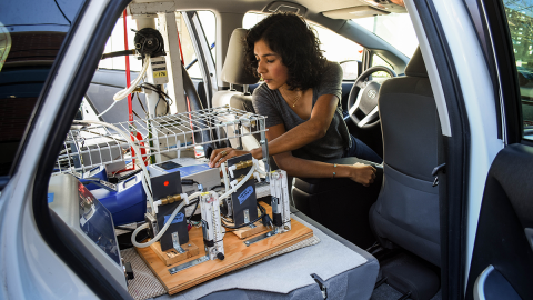 A woman looks at scientific equipment in the back seat of a car.