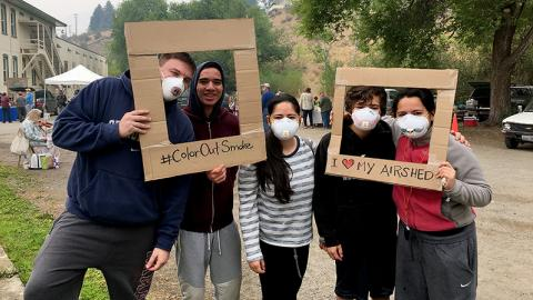 "Five people (four in N95 masks) pose with cardboard picture frame cutouts saying ""#ColorOutSmoke"" and ""I [heart] MY AIRSHED."""