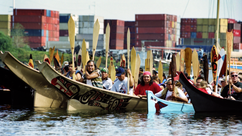 A group of people paddle Native boats on a river past a shipping terminal.