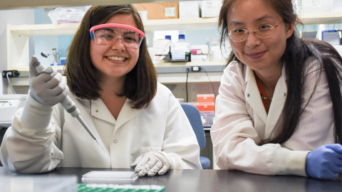 Two women in white lab coats work together in a lab.