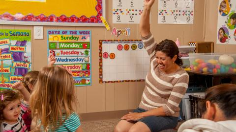 A child care provider sits on the floor raising her hand and smiling with a circle of preschoolers watching.