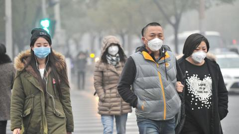 A group of Chinese pedestrians wear face masks while walking in smog.