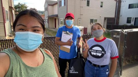 "Three people with face masks on stand in front of a fence with houses in background. Person in middle holds a clipboard and pen, person on right gives a peace sign and is wearing a t-shirt that reads ""SERVE LOCAL."""