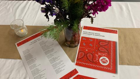 A table with a vase of flowers, a candle, and some printed materials on preventing sexual harassment in agriculture.