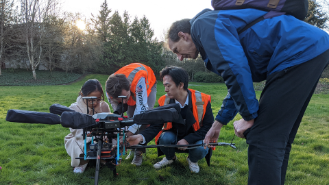 Four people crouching around a large drone in a field surrounded by trees.