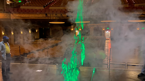A neon green laser light highlights the airflow on the stage of a large theatre space.
