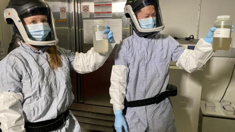 Two lab workers in protective suits and face shields hold up samples of wastewater in plastic bottles.