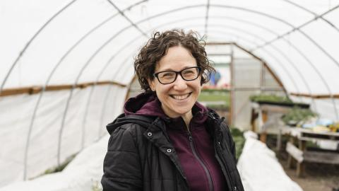Portrait of DEOHS Lecturer Yona Sipos in a greenhouse