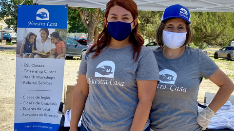 "Two women in ""Nuestra Casa"" T-shirts and face masks stand next to a sign about resources offered by Nuestra Casa in English and Spanish (ESL Classes, Citizenship Classes, Health Workshops, Referral Services)"