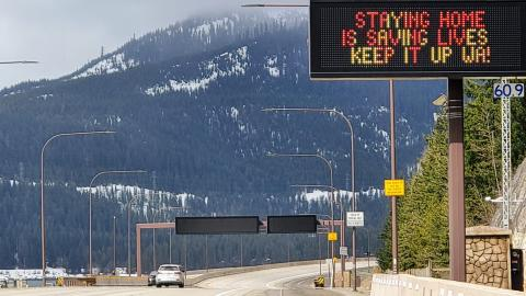 "Two cars driving on otherwise empty Interstate 5 going over Snoqualmie Pass in Washington state, with roadside sign reading ""STAYING HOME IS SAVING LIVES. KEEP IT UP WA!"""