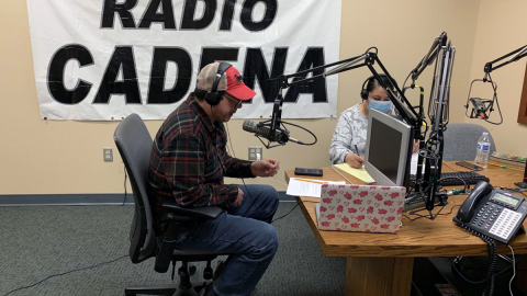 "Two people sit in a radio booth at a table with microphones, with sign ""RADIO CADENA"" behind them."