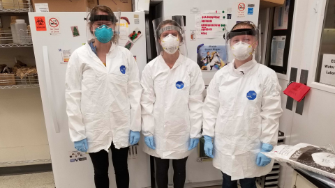 3 women in PPE including face shields, masks, gloves, coats and closed toed shoes.