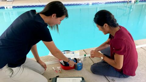 Ali, pictured on the left, assists with a swimming pool inspection.  She and another woman sit on the concrete edge of a chlorinated pool with testing equipment and a clipboard.