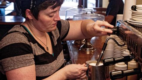 A woman in a coffee shop steams milk while preparing a coffee beverage.