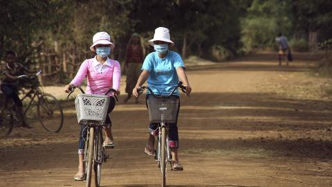 Two women wearing air masks on bicycles on a dirt road.