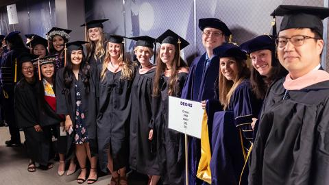 DEOHS Students pose for a photo in the hallway before entering the stadium where the SPH graduation ceremony will take place.