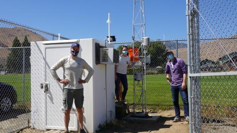3 people wearing face masks stand next to weather monitoring equipment inside a chain-link fence.