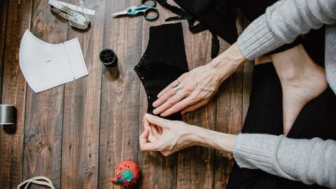 A person (only arms and legs shown) preparing a pattern for a handmade cloth face mask, sticking pins into it from a pincushion with thread, scissors and tape measure in the background.