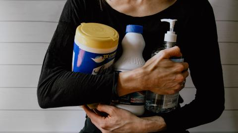 A woman dressed in a black shirt holds several cleaning products in her arms.