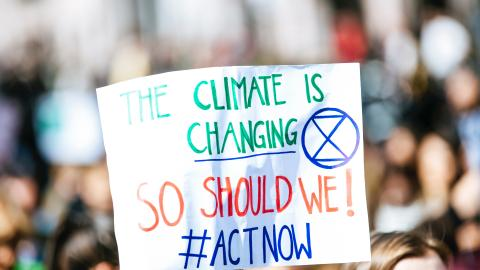 "A white sign held up during a rally says, ""The climate is changing. So should we. Act now!"""