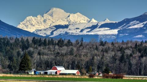A red barn and farmland in the foreground with Mount Baker in the background.
