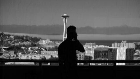 Man talking on phone in front of handrail with downtown seattle in the background.