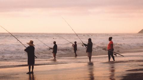Five people fishing at the ocean, standing in the surf with fishing rods.