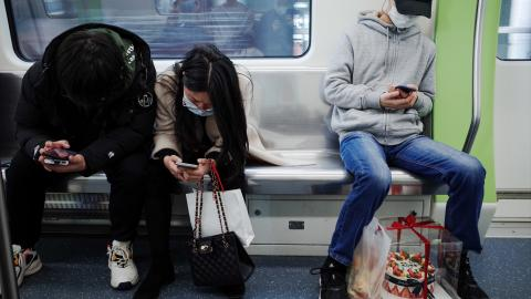 Three people sit on a subway wearing face masks and looking at their phones.