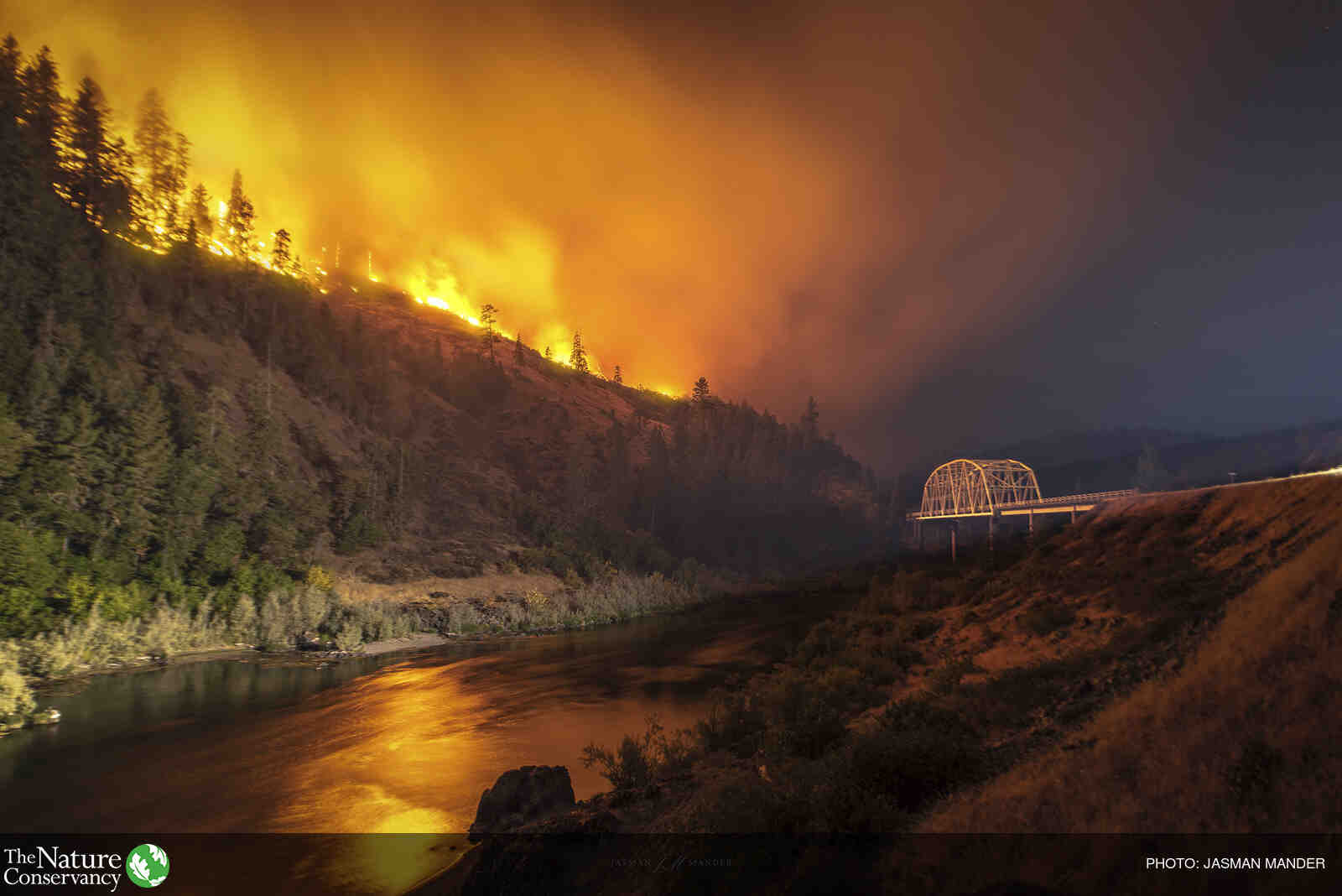 Wildfire on a ridge above a river and bridge.