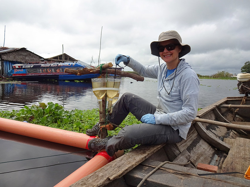 Dr. Rebecca Neumann collects water samples near a floating community in the Peruvian Amazon.