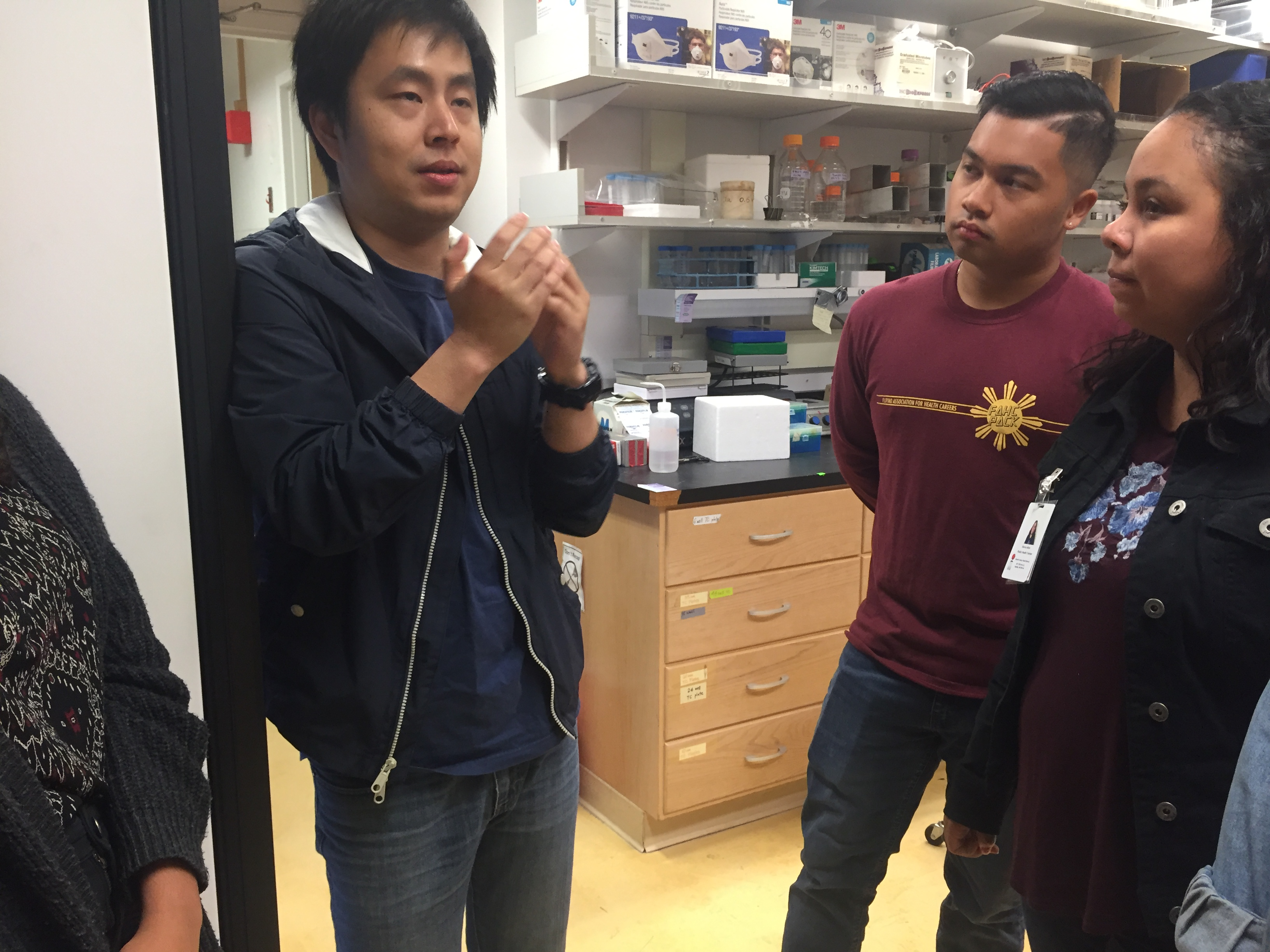 Graduate student, Hao Wang, discusses his research with visiting students in the Xia lab.