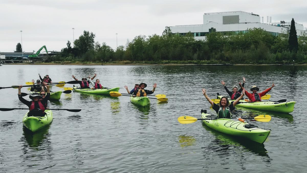 kayakers hold up their paddles