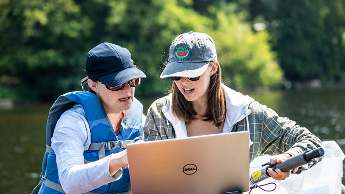 Dr. Neumann points at a laptop with graduate student, Samantha Fung, on a boat in a lake field site.